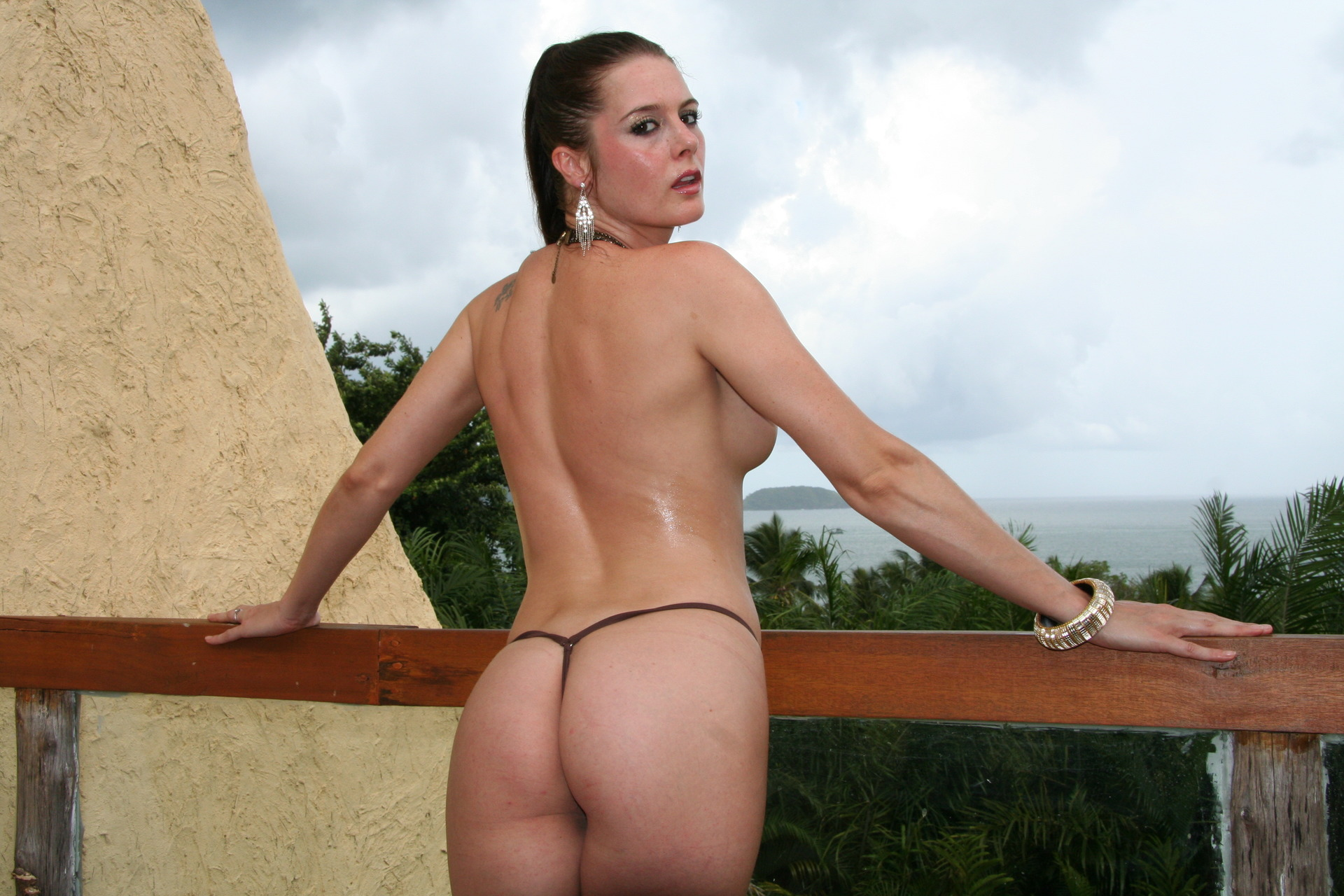karina currie topless turning away from the camera in a black thong on a balcony showing her arse