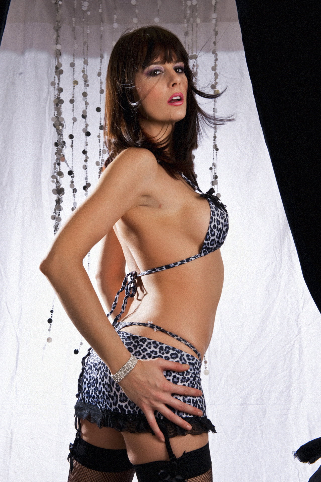 Karina Currie brunette babe in great and black lepoard print bra and skirt with black stocking looking over her shoulder