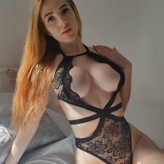 Scarlett Jones in a black lacy body red hair showing off her big tits very slim facing the camera