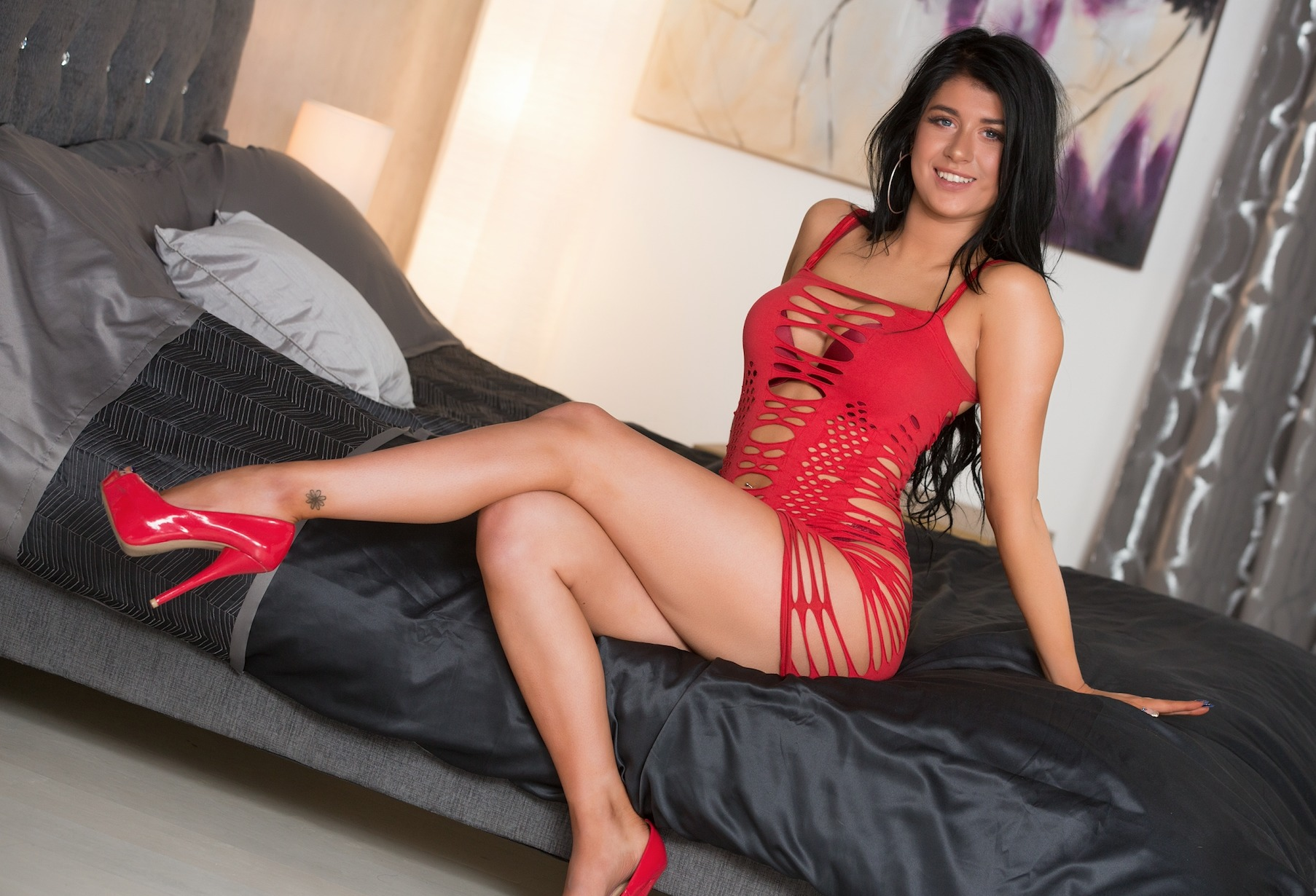 Atlanta brunette sitting on the bed legs crossed in red heels and a red lingerie dress looking seductively with a smile