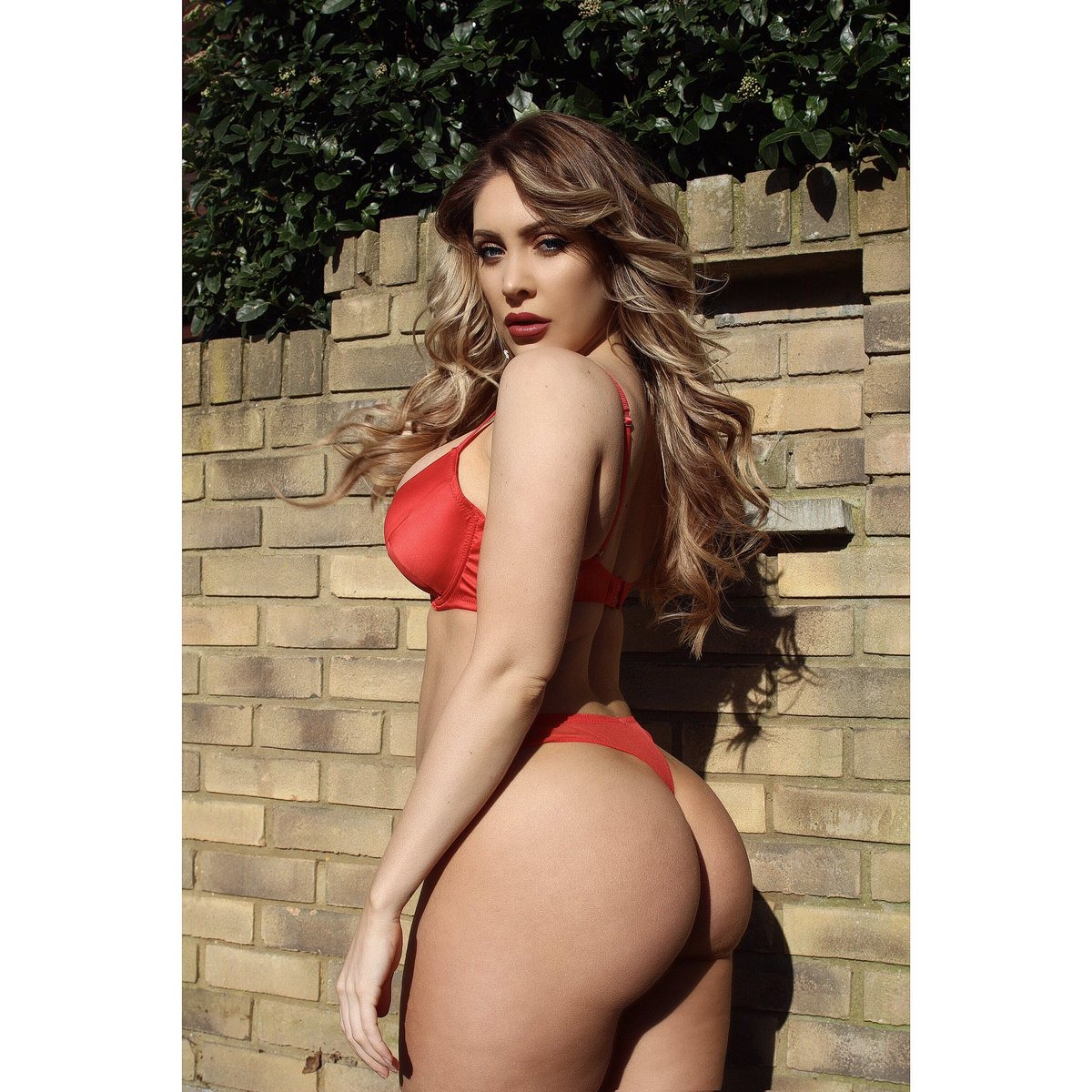 Ashley Emma hot blonde standing outdoors side on looking over shoulder wearing red bra and knickers curvy arse