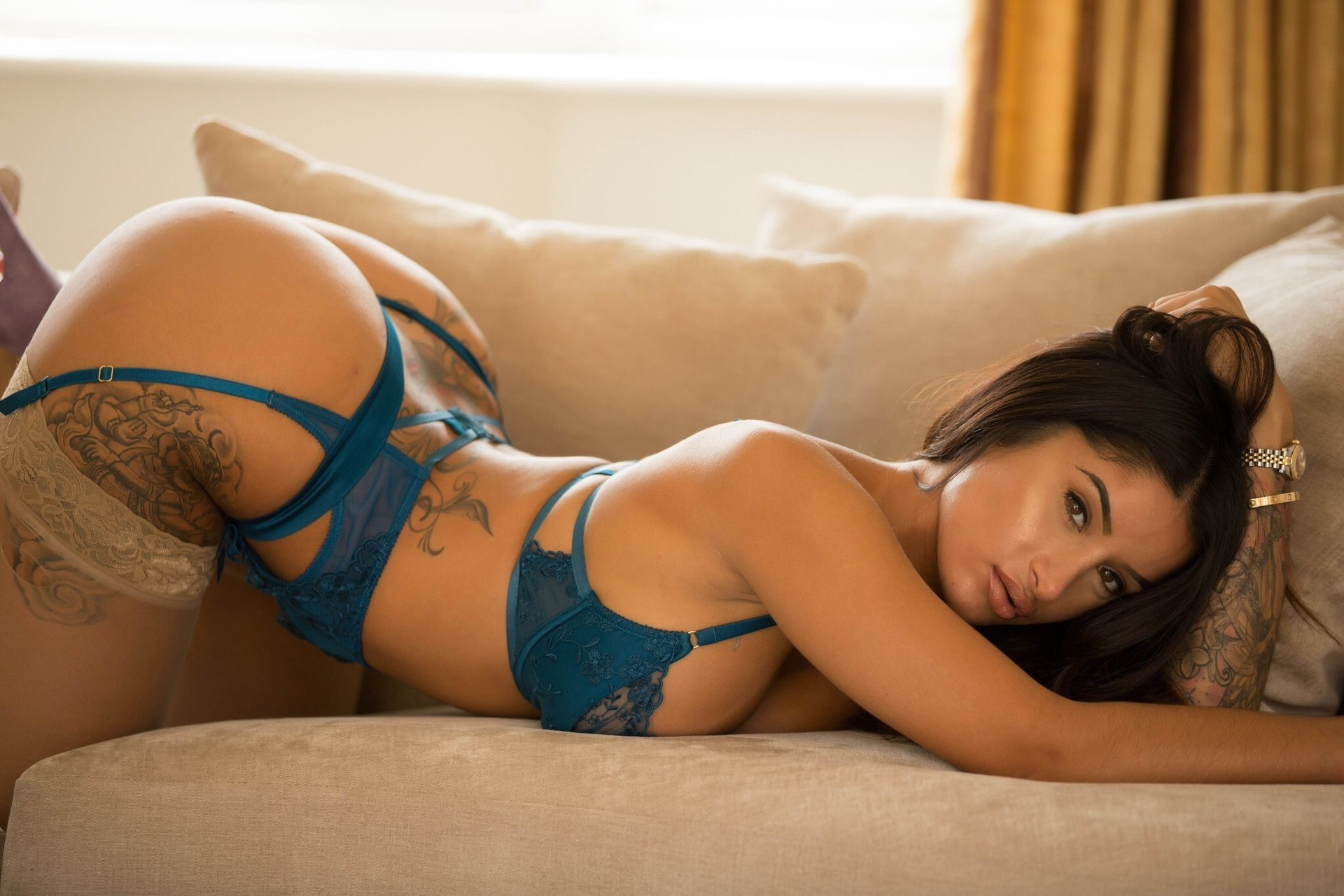 Preeti on all fours on a sofa in green bra and knickers and skin colour stockings bent over arse in the air