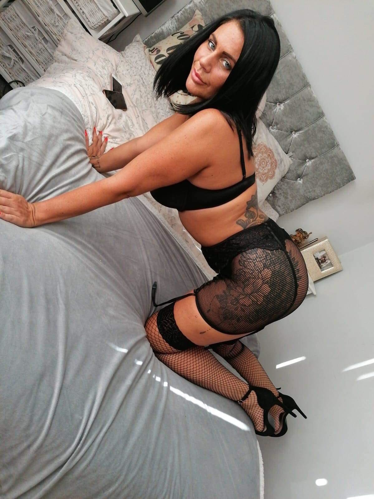 Curvy cam girl Layla fox bending over on top of her bed in her sexy fishnets.