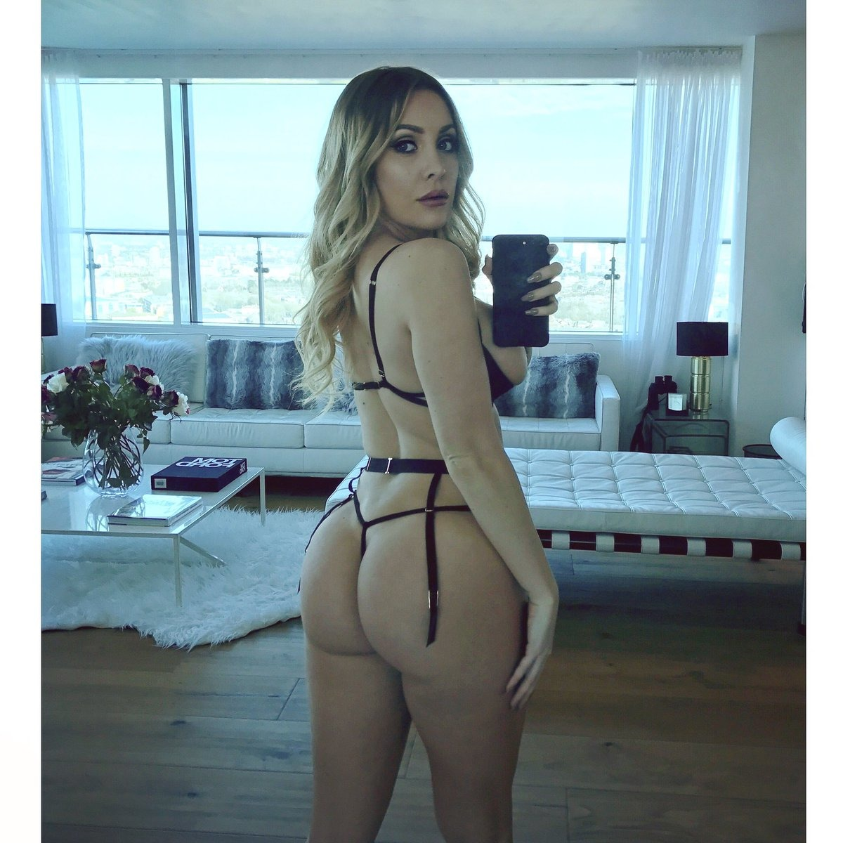 Ashley Emma standing mirror selfie of her figure from behind showing her bum in white and black lingerie and suspenders