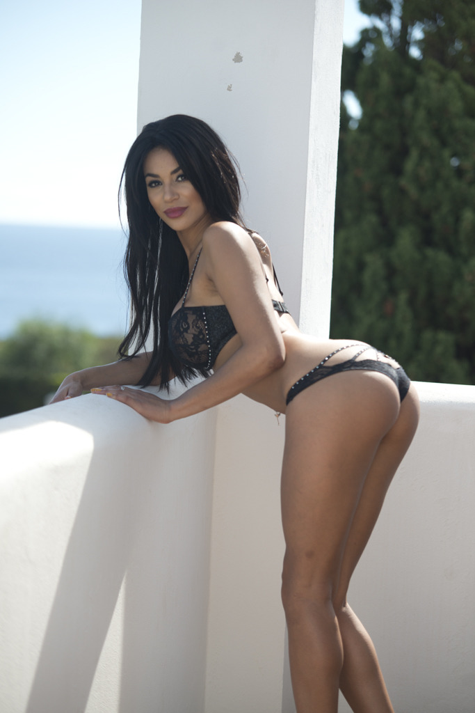olivia berzinc in black underwear bending over the balcony in her stilettos showing her arse to the camera