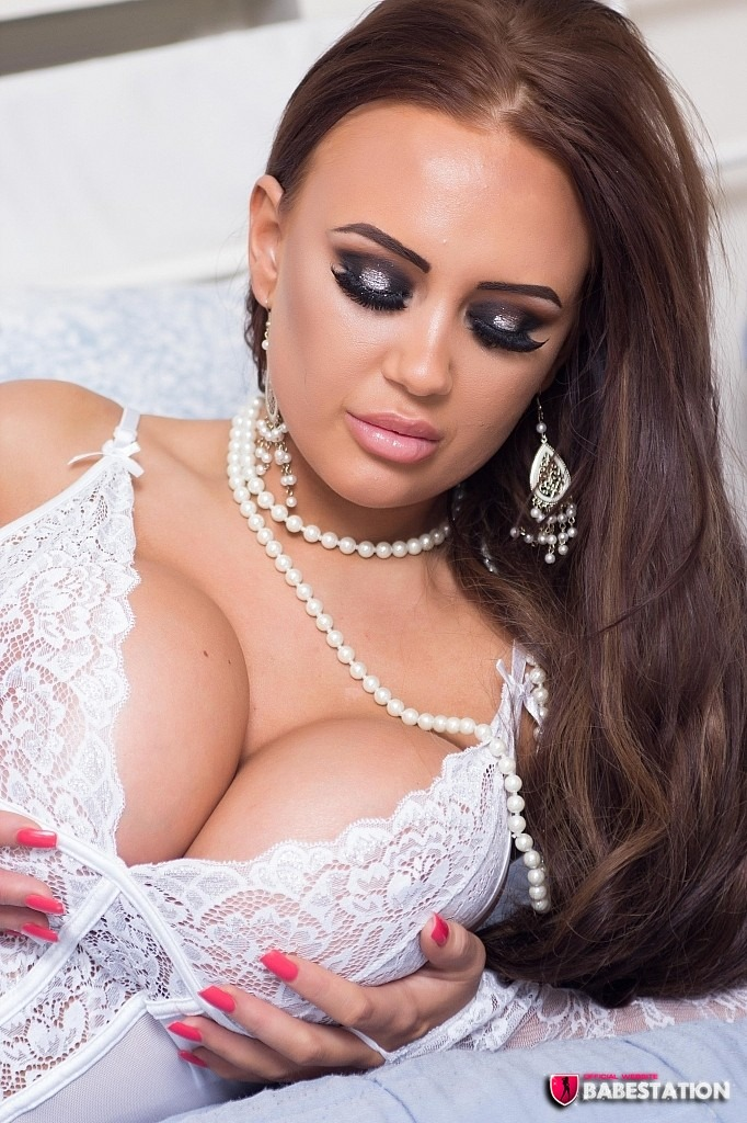 danni levy busty brunette babe wearing a white lacy top holding onto her large breasts