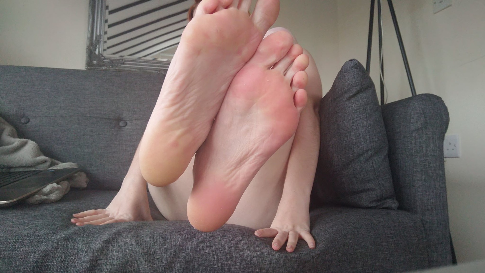scarlett jones with the soles of her feet to the camera flexing her toes, pale skin and wrinkled soles