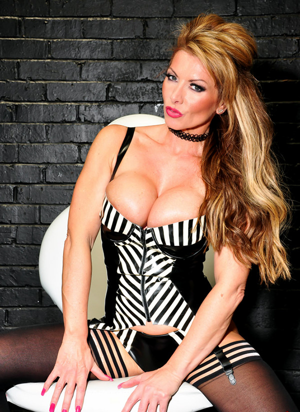 Lynda Leigh sitting with legs spread in black and white low cut busty dress showing her knickers and stockings