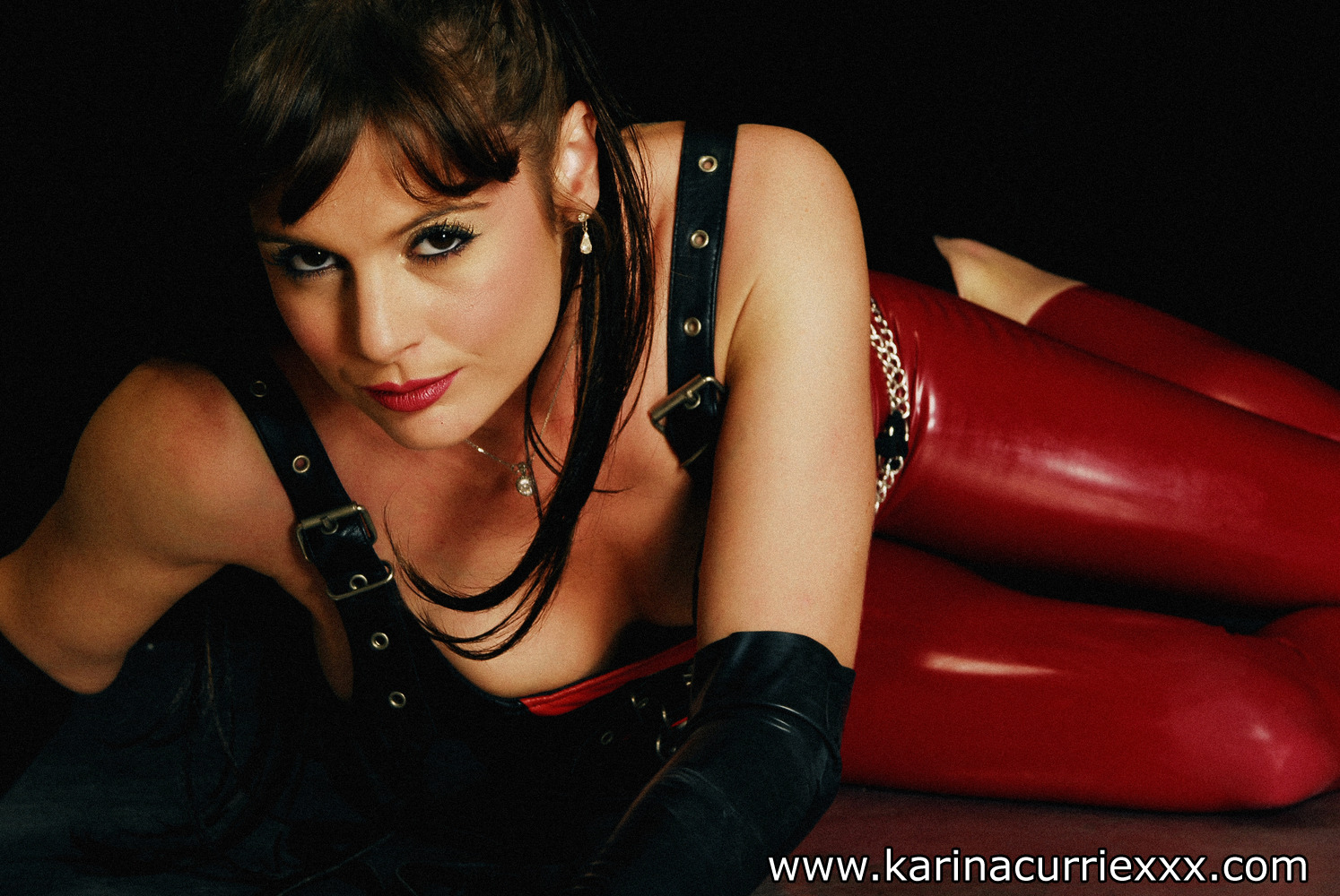 karina currie in red leather latex trouser and black buckled top laying on the floor smiling at the camera