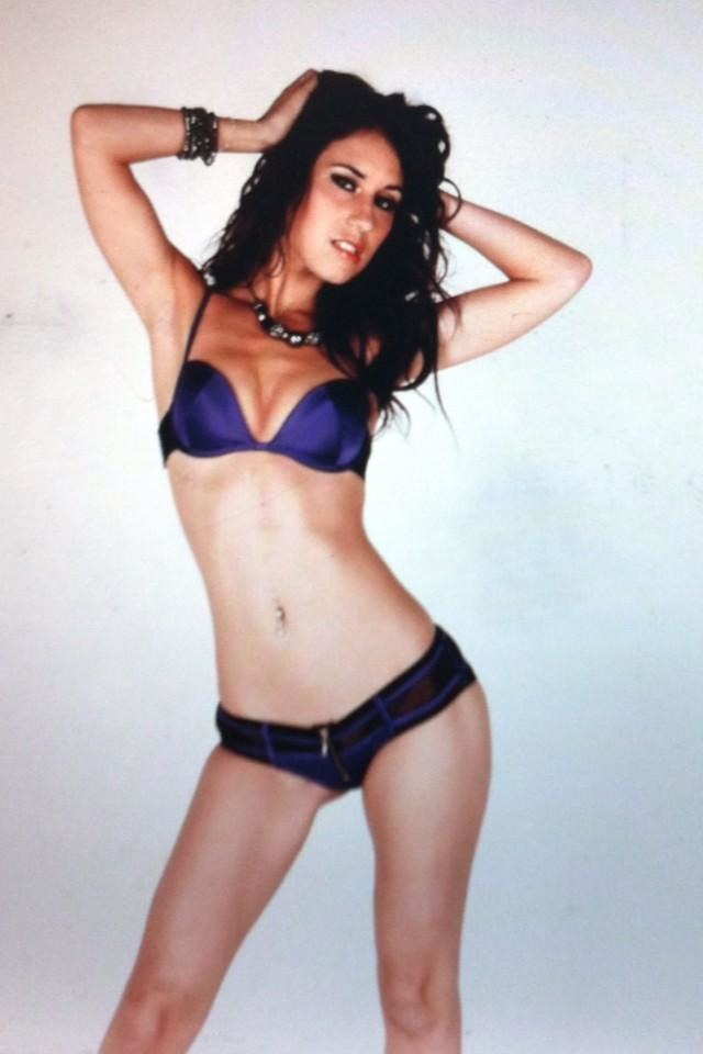 Jess West slim brunette standing in purple bra and knickers with arms up by her head and legs apart