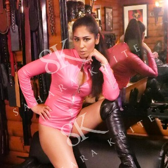 sahara knite in pink latex body suit and black latex boots slim brunette posing for the camera