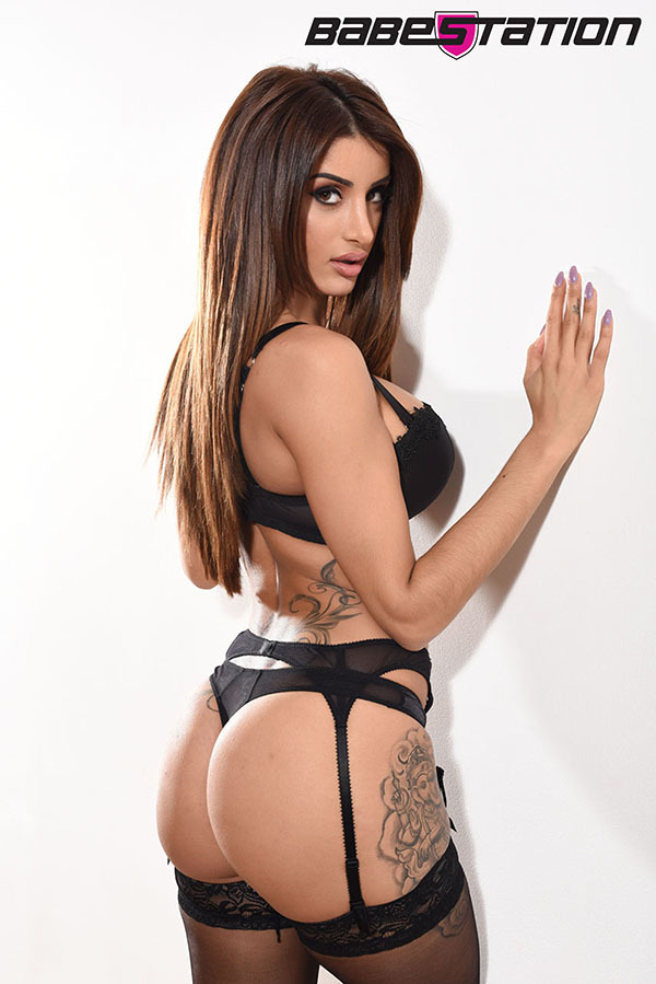 Preeti standing up against a wall in black lingerie and stockings, slim figure brunette