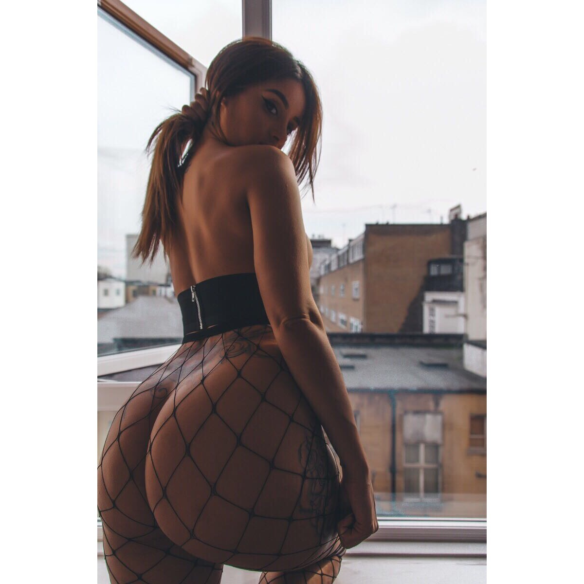 Preeti slim figure with a big round arse looking over her shouder wearing fishnet leggings and a tight top