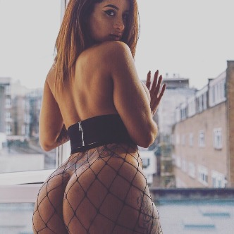 Preeti looking over her shoulder in black top no knickers and fishnets showing off her slim figure big bum
